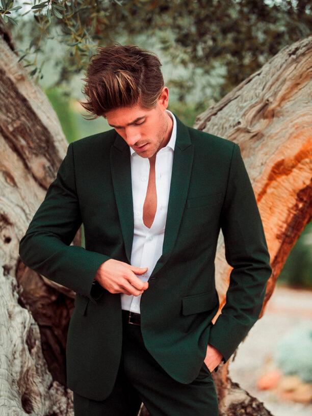 Traje de hombre entallado en tono verde botella.