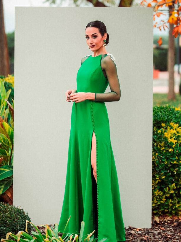 Vestido largo verde esmeralda con abertura abotonada en la falda y aplicaciones en los hombros.